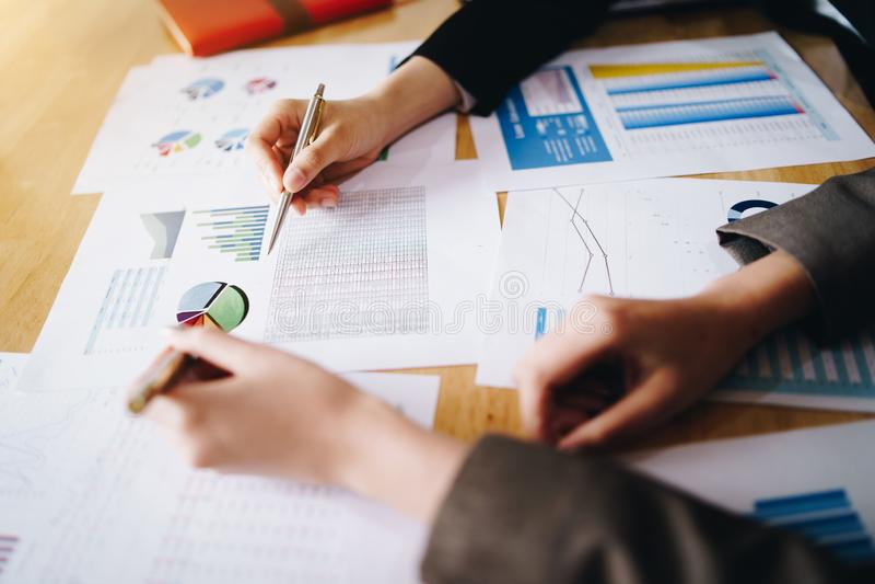 Empresaria que señala la pluma en el documento de negocio en la sala de reunión Cartas y gráficos de los datos de la discusión y  imagen de archivo libre de regalías