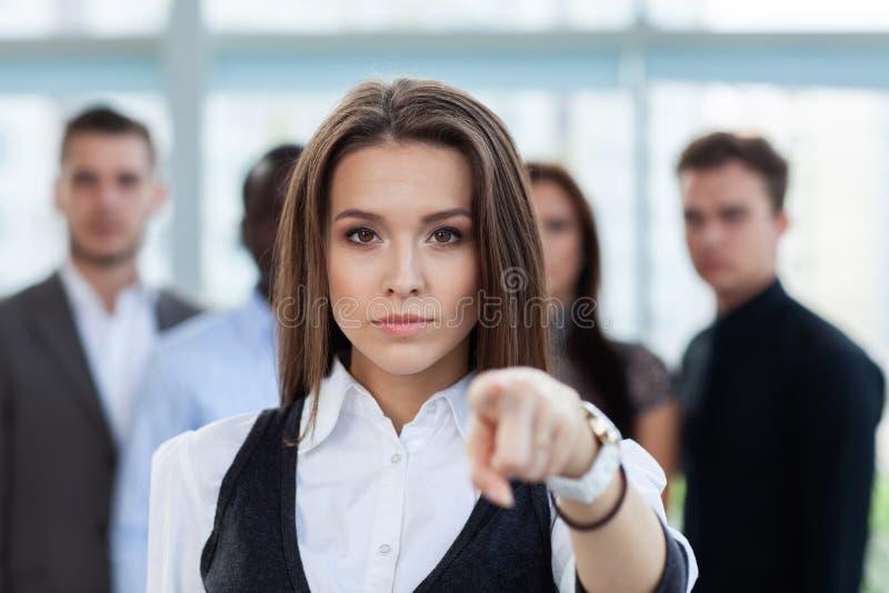 Empresaria que señala su finger en usted en el fondo de hombres de negocios imagen de archivo