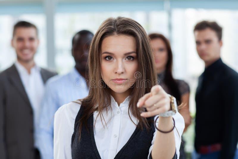 Empresaria que señala su finger en usted en el fondo de hombres de negocios imagenes de archivo