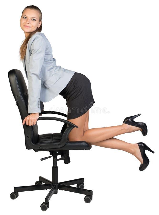 Empresaria que se arrodilla en la silla de la oficina, mirando fotos de archivo