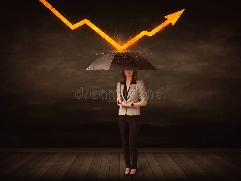 Empresaria que se coloca con el paraguas que guarda la flecha anaranjada foto de archivo