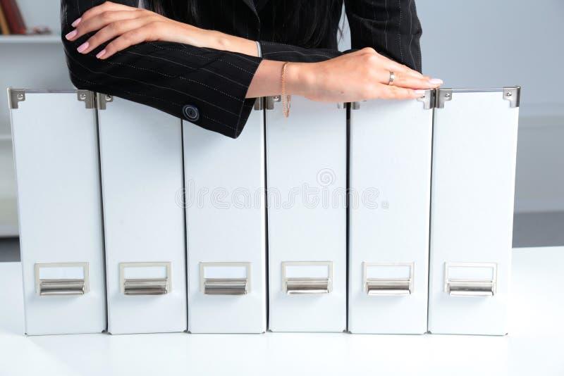 Empresaria que se inclina en una carpeta en la oficina fotografía de archivo
