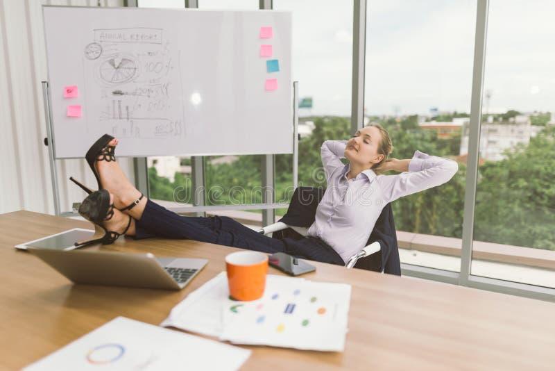 Empresaria que se relaja con los pies para arriba en el escritorio en oficina creativa Rel?jese y reclinaci?n fotos de archivo