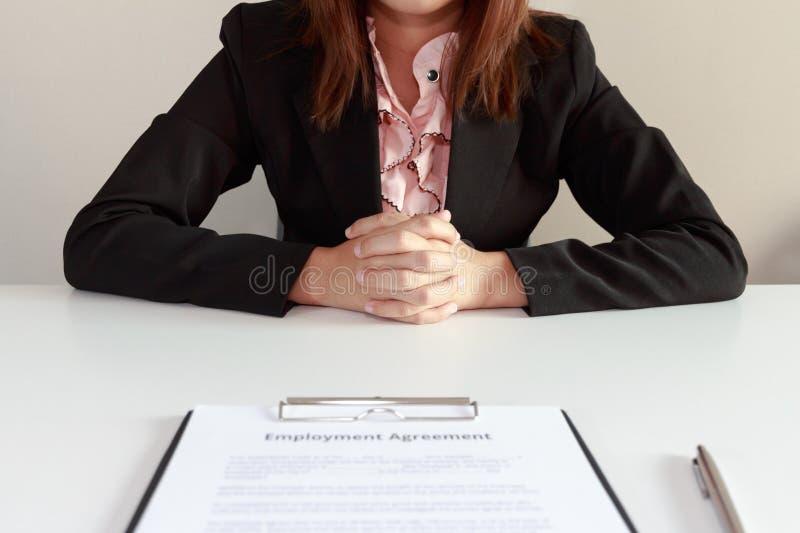 Empresaria que se sienta con el acuerdo de empleo delante de ella foto de archivo libre de regalías