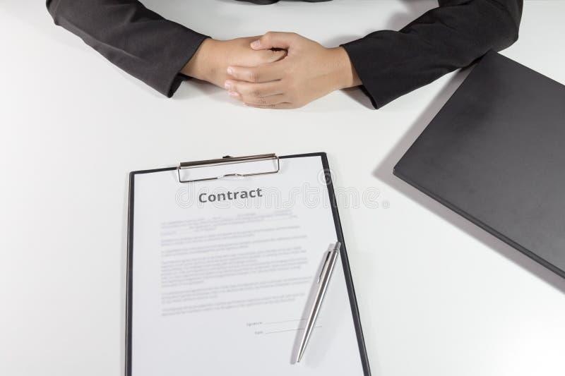 Empresaria que se sienta con el contrato delante de ella fotos de archivo