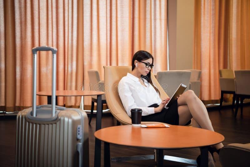 Empresaria que se sienta en el sal?n del negocio del aeropuerto, esperando el vuelo Vidrios que llevan sonrientes de la mujer que imagen de archivo libre de regalías