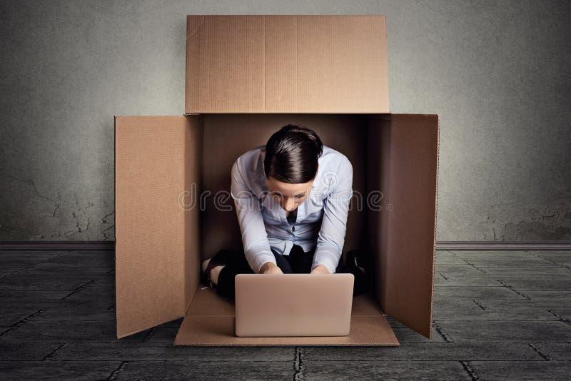 Empresaria que se sienta en la caja del cartón que trabaja en el ordenador portátil imagenes de archivo