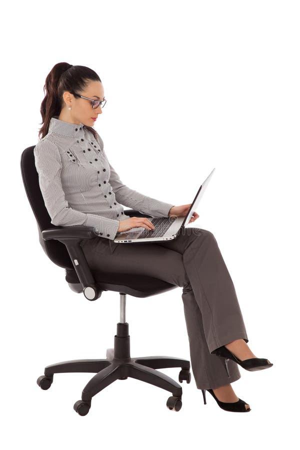 Empresaria que se sienta en la silla de la oficina con el ordenador portátil imagen de archivo libre de regalías