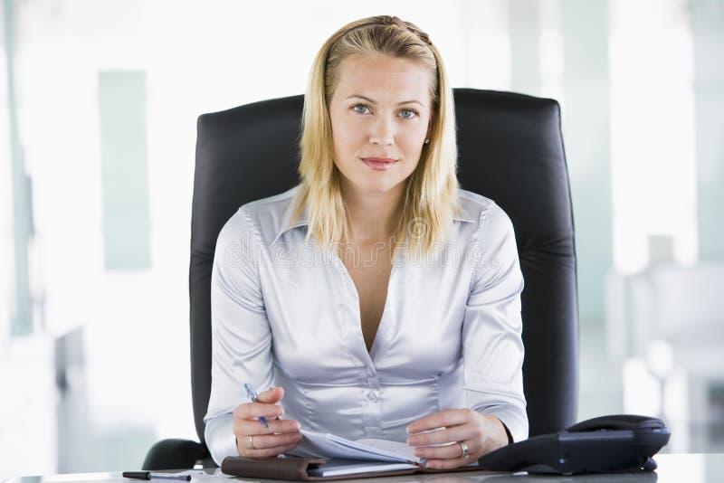 Empresaria que se sienta en oficina con personal fotos de archivo