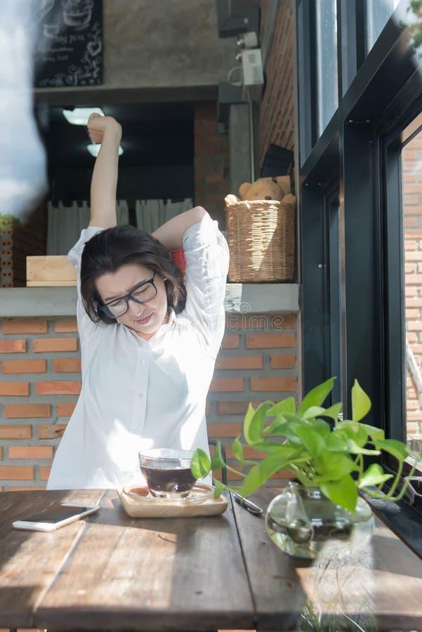 Empresaria que se sienta en su lugar de trabajo y que estira sus manos sobre su cabeza Empleado de sexo femenino cansado en el lu imagen de archivo