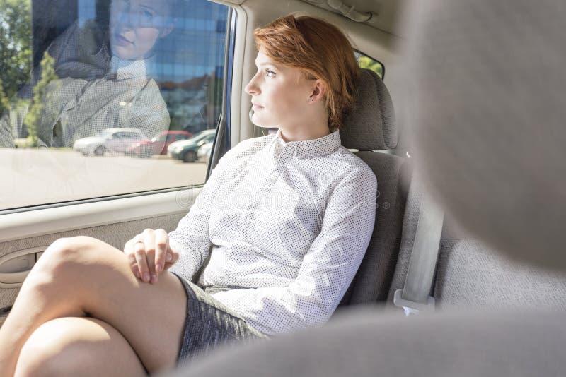 Empresaria que se sienta en un asiento trasero en un taxi imagen de archivo