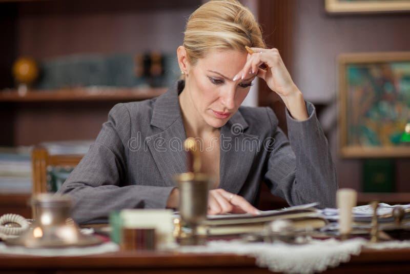 Empresaria que se sienta en una tabla en la oficina y el trabajo imagenes de archivo