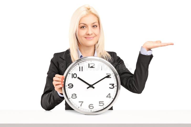 Empresaria que sienta y que sostiene un reloj de pared imágenes de archivo libres de regalías
