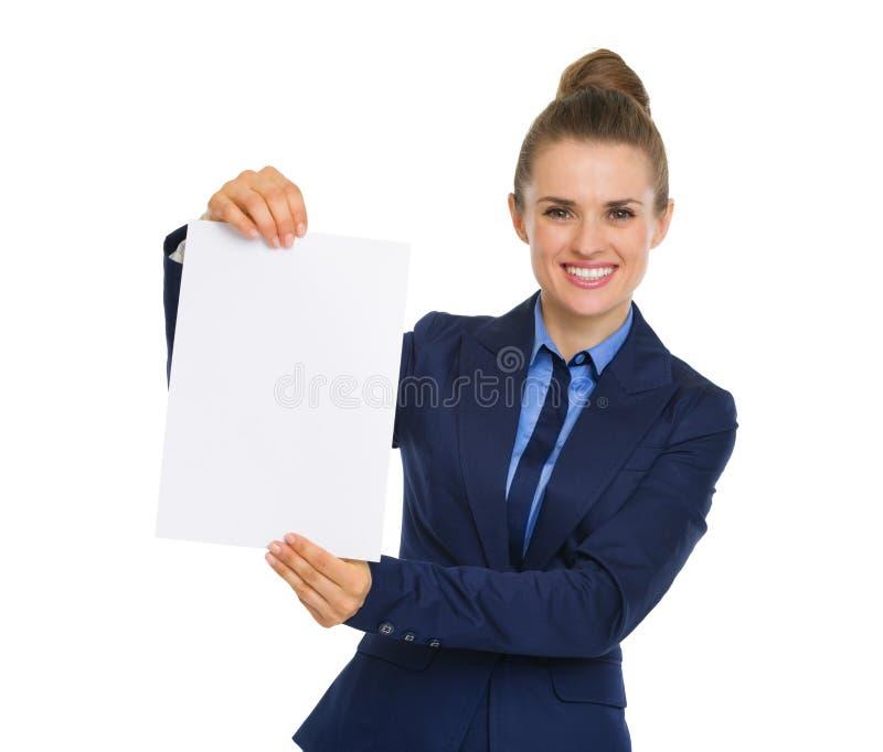 Empresaria que sonríe y que soporta un trozo de papel en blanco imágenes de archivo libres de regalías