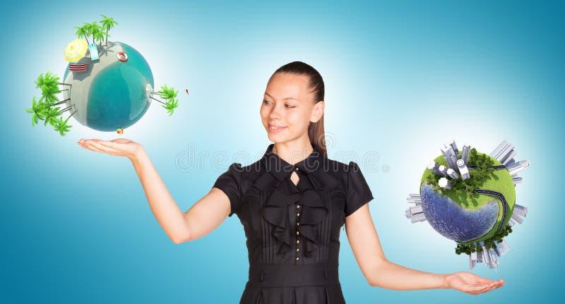 Empresaria que sostiene dos globos de la tierra foto de archivo