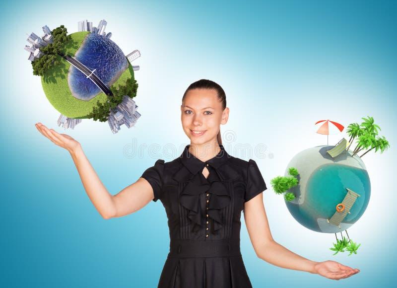 Empresaria que sostiene dos globos de la tierra imágenes de archivo libres de regalías