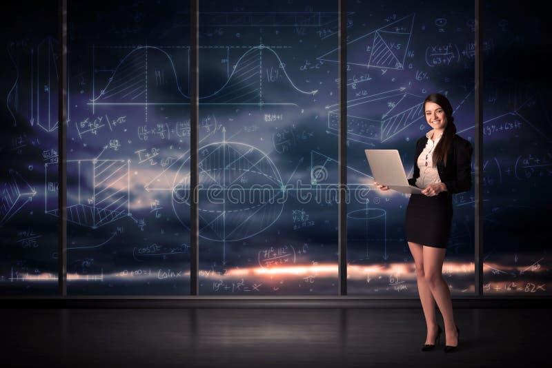 Empresaria que sostiene el ordenador portátil en sitio de la oficina con las cartas del gráfico encendido fotos de archivo