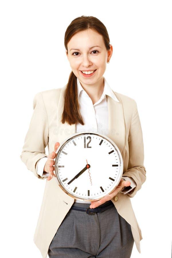 Empresaria que sostiene el reloj Aislado imagen de archivo