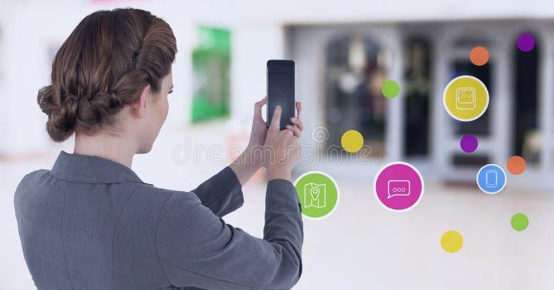 Empresaria que sostiene el teléfono móvil con los apps en alameda de compras imagen de archivo libre de regalías