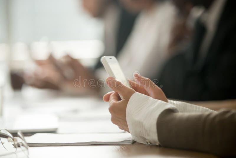 Empresaria que sostiene el teléfono móvil en la reunión de la oficina, cierre encima de v fotos de archivo