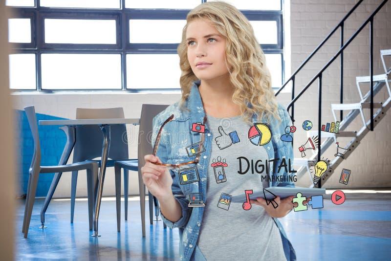 Empresaria que sostiene la tableta rodeada por el texto y los iconos digitales del márketing fotografía de archivo libre de regalías