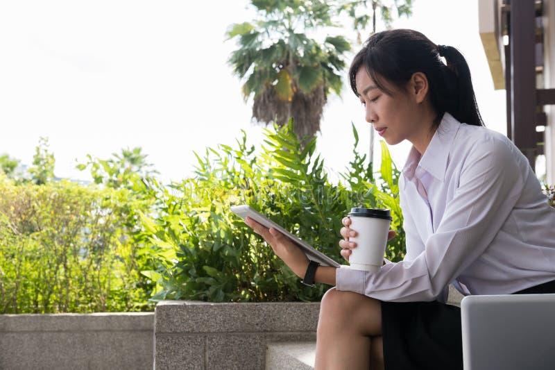 Empresaria que sostiene la tableta y el café digitales fuera del bui de la oficina fotografía de archivo