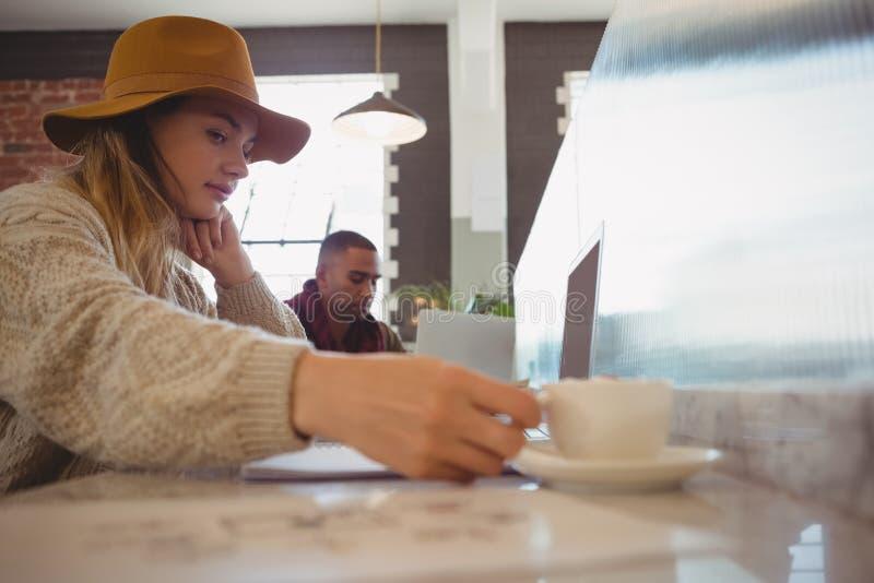 Empresaria que sostiene la taza de café en el contador foto de archivo
