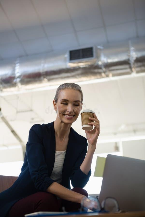 Empresaria que sostiene la taza disponible mientras que se sienta con el ordenador portátil en la tabla imagen de archivo
