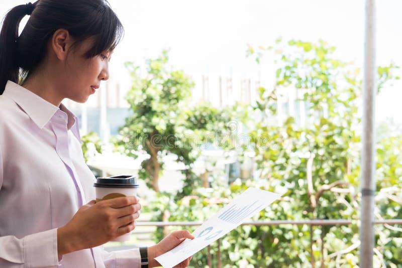 Empresaria que sostiene outsi del gráfico de la taza de café y del resumen financiero imagen de archivo