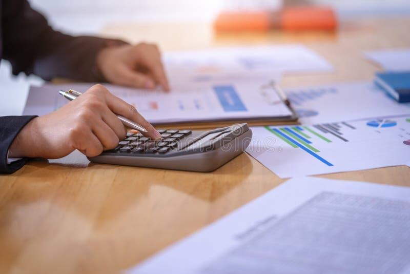 Empresaria que sostiene una pluma y analizar el plan de comercializaci?n con la calculadora en el escritorio de madera en oficina imagen de archivo libre de regalías