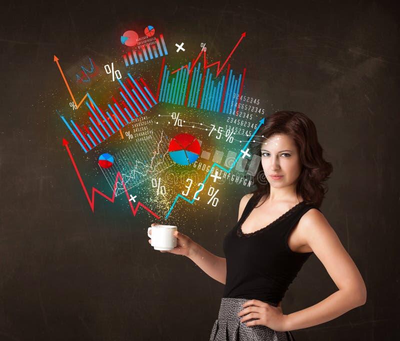 Empresaria que sostiene una taza blanca con los diagramas y los gráficos imagen de archivo