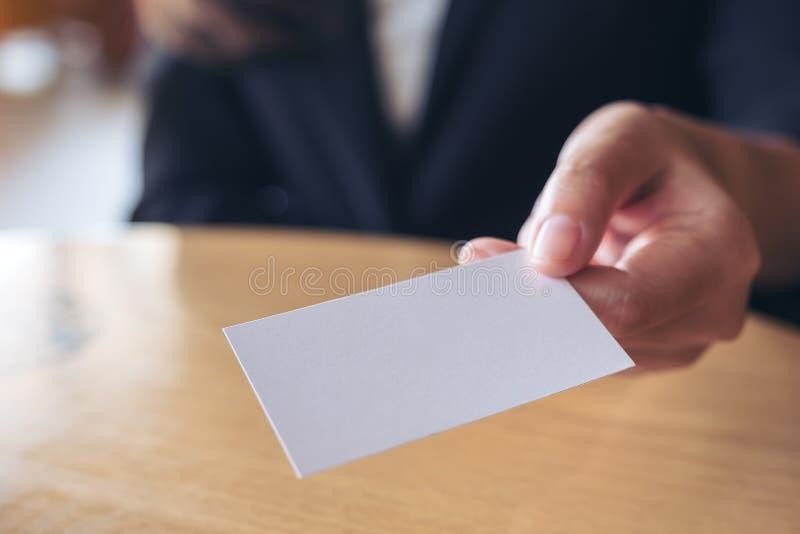 Empresaria que sostiene y que da una tarjeta de visita vacía alguien en la tabla imagenes de archivo