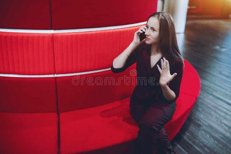 Empresaria que tiene llamada vía smartphone en oficina fotos de archivo libres de regalías