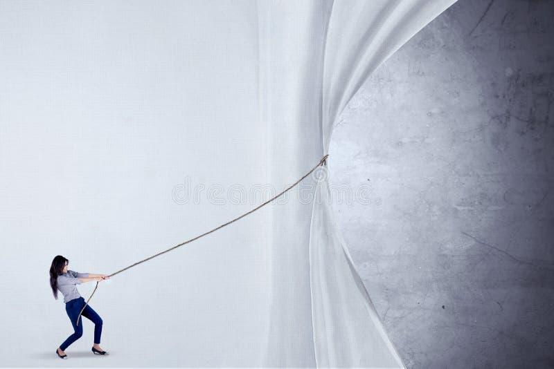 Empresaria que tira de la cortina con la cuerda foto de archivo libre de regalías