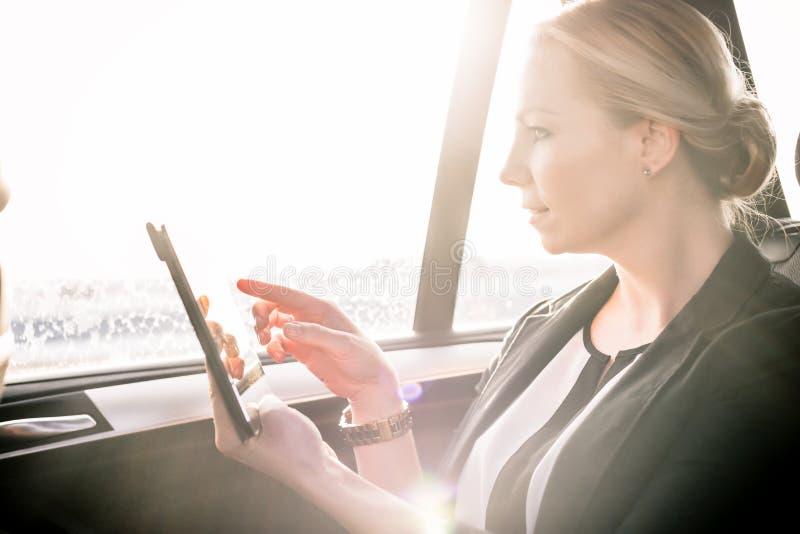 Empresaria que toca la pantalla digital de la tableta en coche fotos de archivo libres de regalías