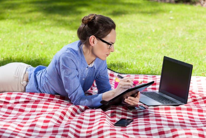 Empresaria que trabaja al aire libre con su ordenador portátil foto de archivo