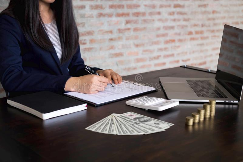 Empresaria que trabaja con el documento de la declaraci?n de renta en la tabla de madera Concepto del asunto foto de archivo libre de regalías