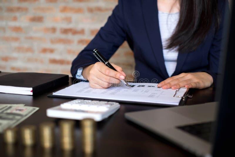 Empresaria que trabaja con el documento de la declaraci?n de renta en la tabla de madera Concepto del asunto fotos de archivo