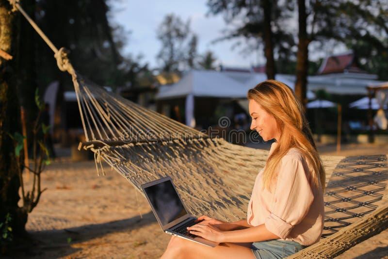 Empresaria que trabaja con el ordenador portátil y que se sienta en la arena en hamaca de mimbre fotos de archivo libres de regalías