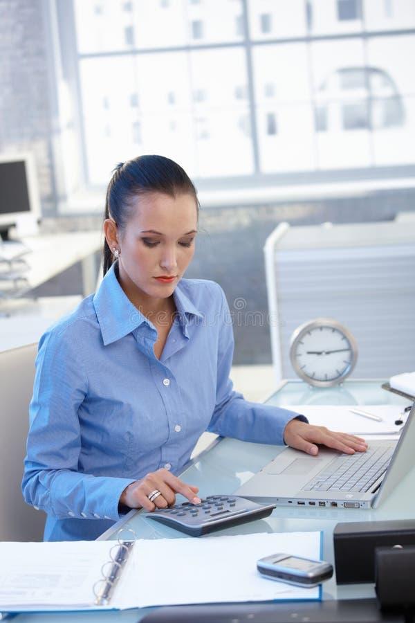 Empresaria que trabaja en el escritorio con la calculadora imágenes de archivo libres de regalías