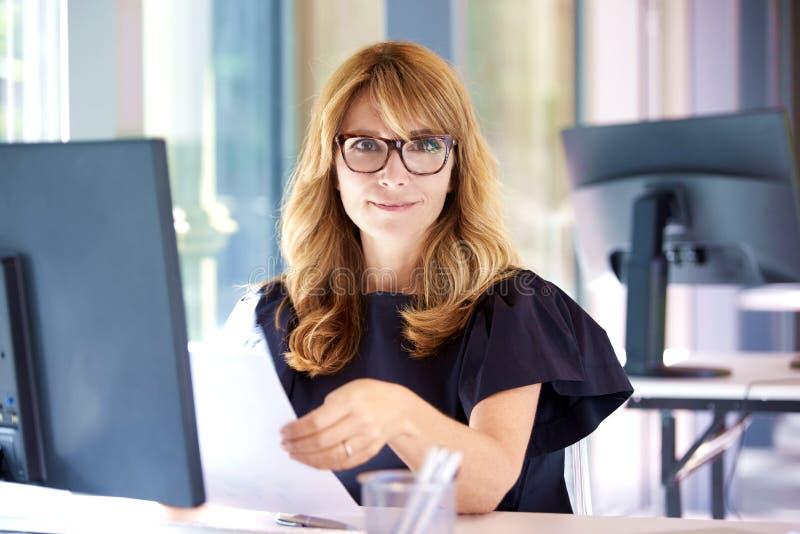 Empresaria que trabaja en el ordenador en la oficina imagen de archivo libre de regalías