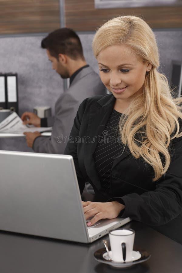Empresaria que trabaja en el ordenador portátil fotos de archivo