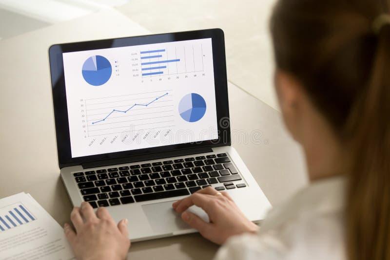 Empresaria que trabaja en el ordenador portátil, analizando estadísticas, software imagen de archivo libre de regalías