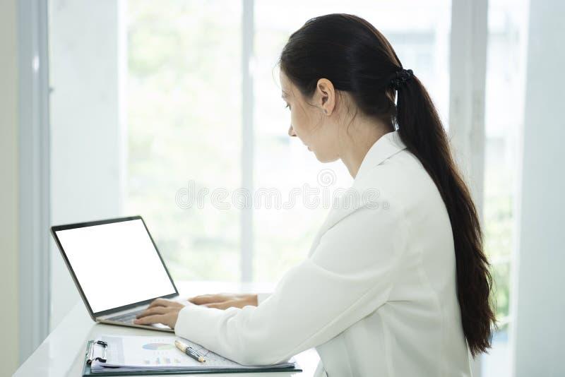 Empresaria que trabaja en el ordenador portátil con la pantalla blanca vacía imagen de archivo