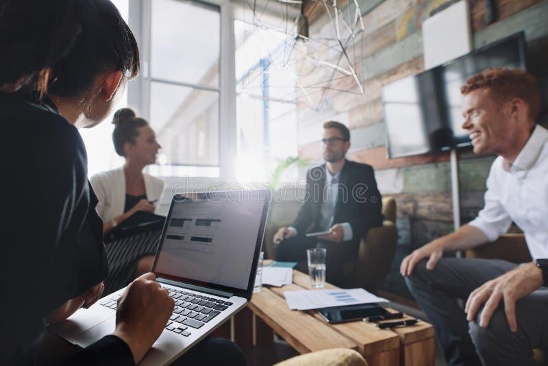 Empresaria que trabaja en el ordenador portátil en la reunión imagen de archivo