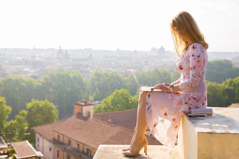 Empresaria que trabaja en el ordenador portátil en madrugada con panorama de la ciudad en fondo imagen de archivo