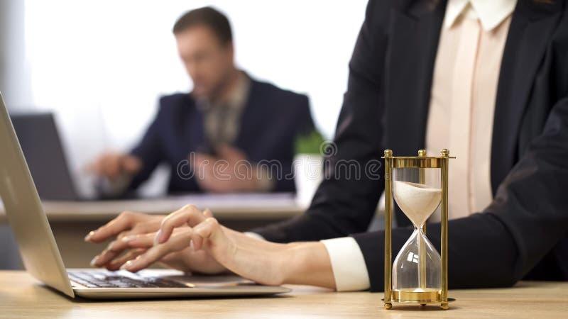 Empresaria que trabaja en el ordenador, reloj de arena que gotea, anticipación del resultado foto de archivo libre de regalías