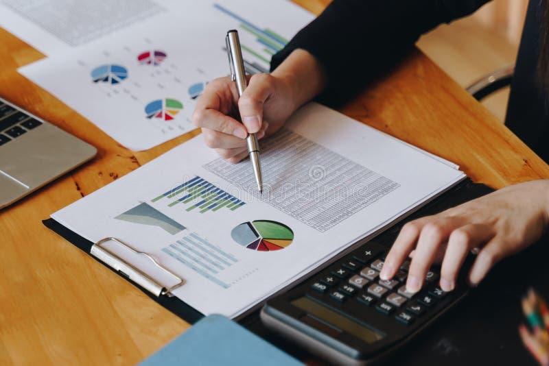 Empresaria que trabaja en la calculadora para calcular informe financiero de los datos de negocio sobre la tabla de madera imágenes de archivo libres de regalías