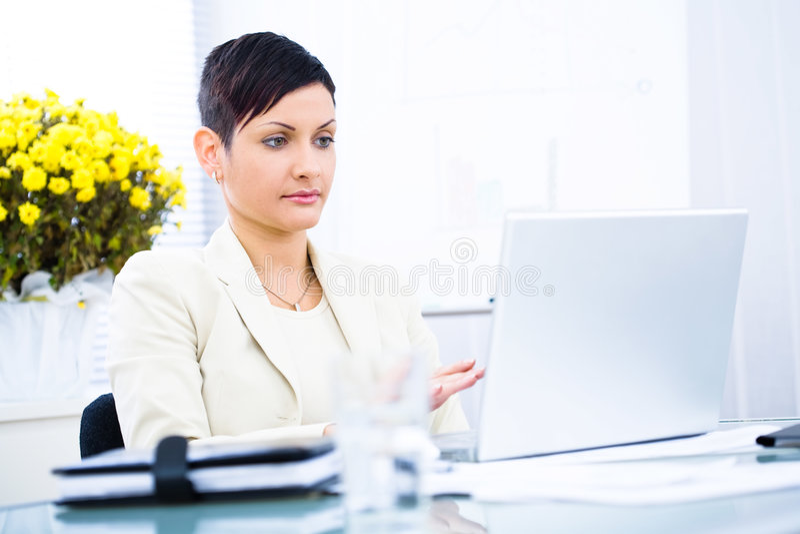 Empresaria que trabaja en la computadora portátil fotografía de archivo