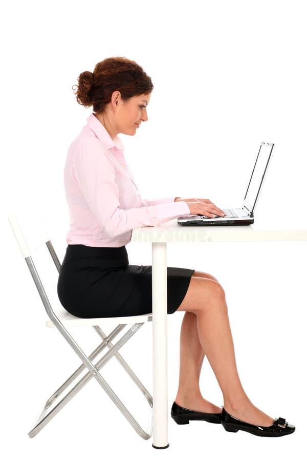 Empresaria que trabaja en la computadora portátil imagen de archivo